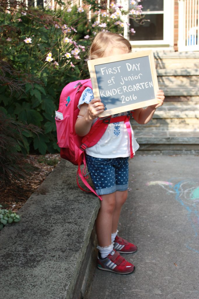 a little girl with large backpack and face covered with small chalkboard that says first day of junior kindergarten