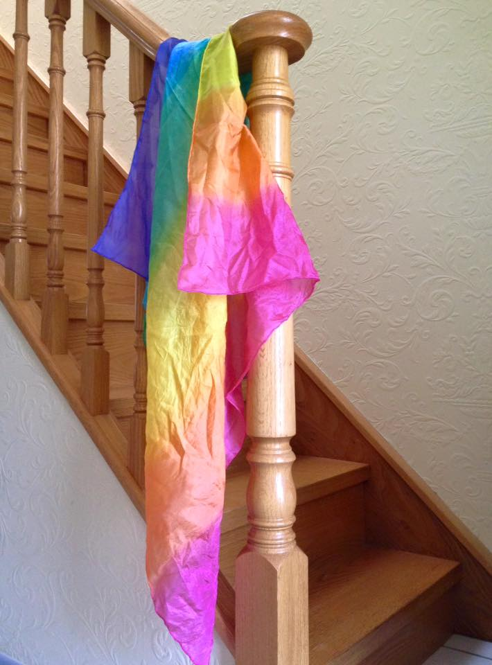 A silk scarf in rainbow colours is draped over our stairway banister